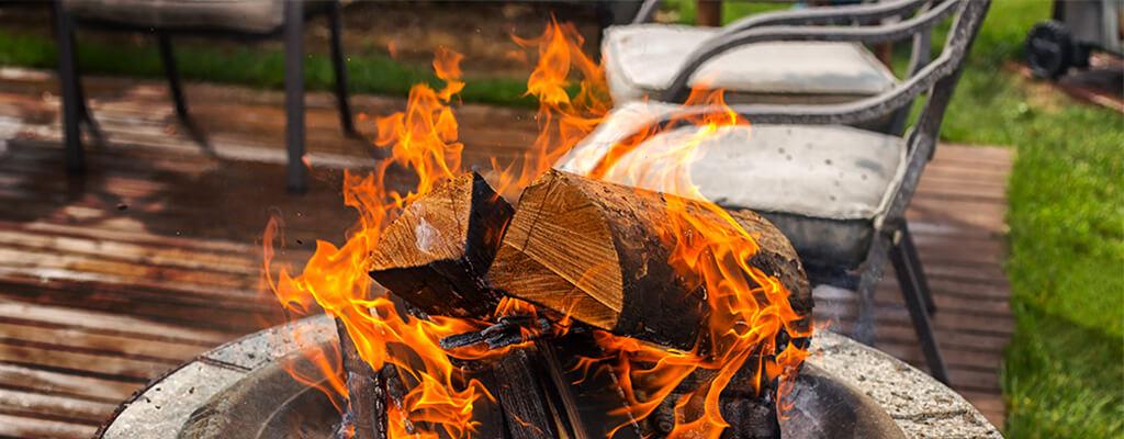 Feuerschale mit loderndem Feuer auf hölzerner Terrasse mit silbernen Stühlen und einem Stück grünen Rasen im Hintergrund
